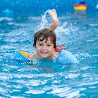 Sweet little boy, swimming in big swimming pool, summrtime