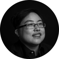 Black and white image of Lydia X. Z. Brown, a young East Asian person with glasses, smiling and laughing, looking slightly away from the camera. Photo by Colin Pieters.